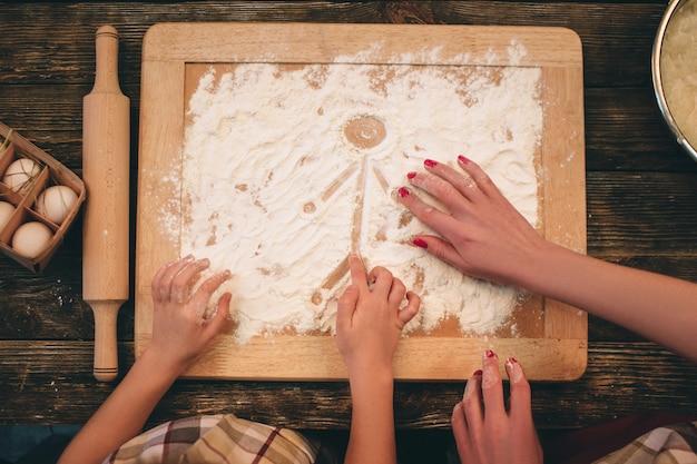 Familie, die selbst gemachte kuchen-, mutter- und tochterhände im mehl auf einer tabelle kocht.