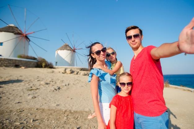 Familie, die selfie mit einem stock vor windmühlen am populären touristengebiet auf mykonos-insel, griechenland nimmt