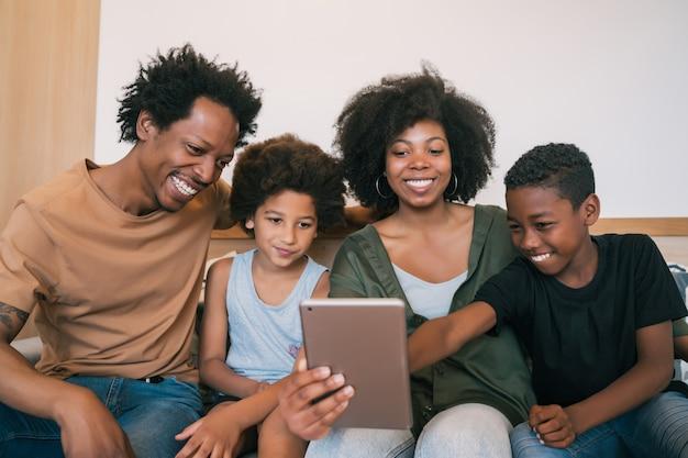 Familie, die selfie zusammen mit tablette zu hause nimmt.