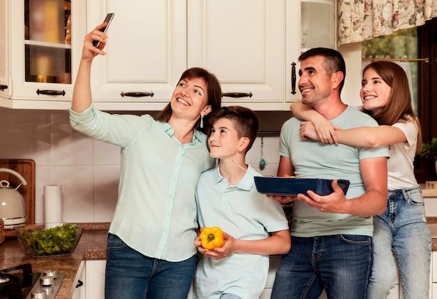 Familie, die selfie zusammen nimmt, während abendessen vorbereitet