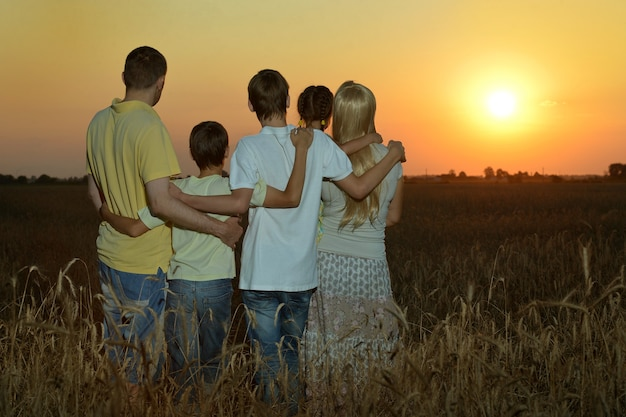 Familie, die sich bei sonnenuntergang im feld ausruht, rückansicht?