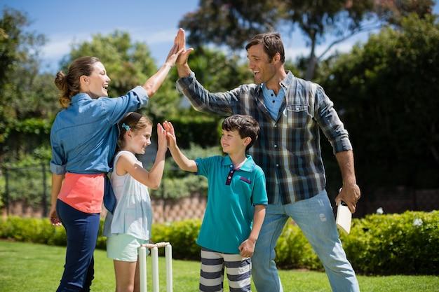 Familie, die sich gegenseitig high five gibt, während sie cricket spielt