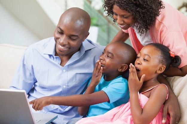 Familie, die sich zusammen auf dem sofa unter verwendung des laptops entspannt