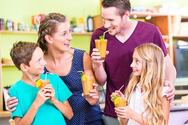 Familie, die smoothie oder saft in der inländischen küche trinkt