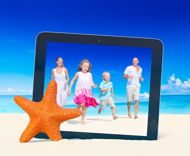 Familie, die spaß auf dem strand mit tabletten-pc-rahmen hat.
