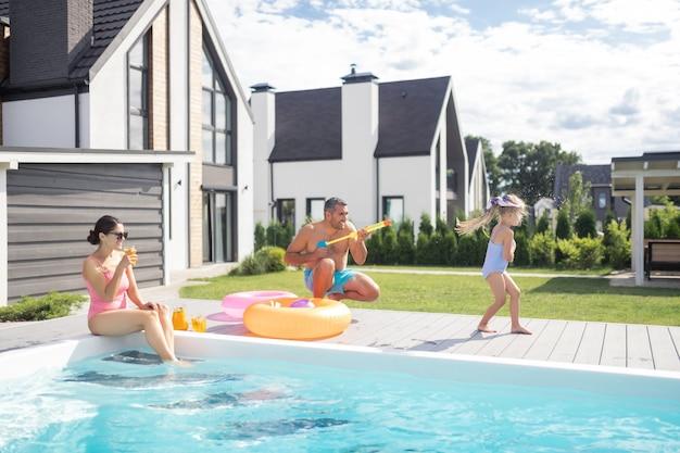 Familie, die spaß hat. glückliche familie, die am wochenende spaß beim chillen in der nähe des schwimmbades hat