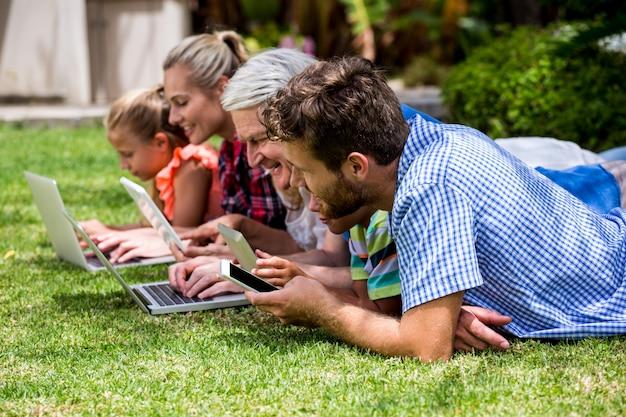 Familie, die technologien bei der entspannung am park einsetzt