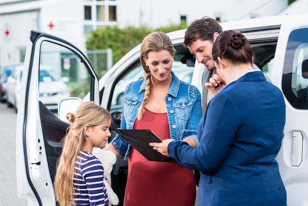 Familie, die vom kaufenden auto des verkäufers beraten wird
