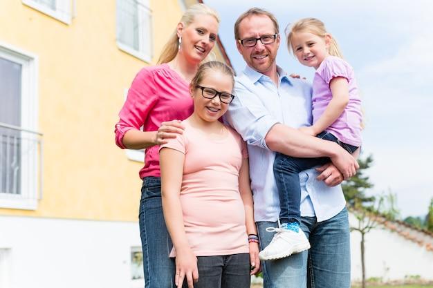 Familie, die vor haus oder haus steht