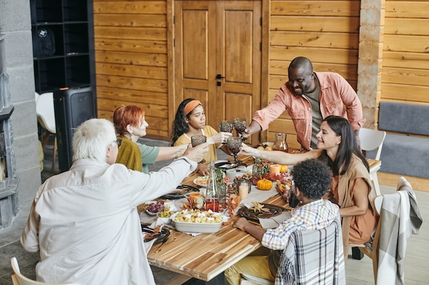 Familie, die während des abendessens am tisch anstößt