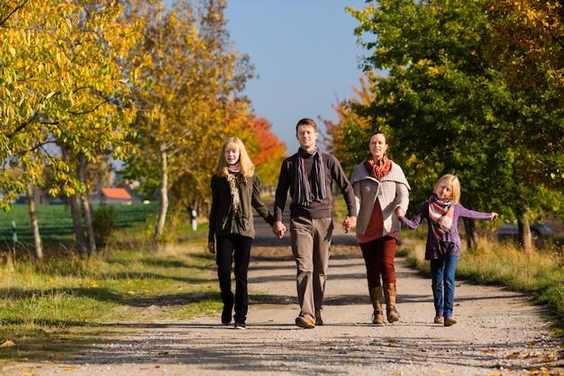 Familie, die weg vor bunten bäumen im herbst hat