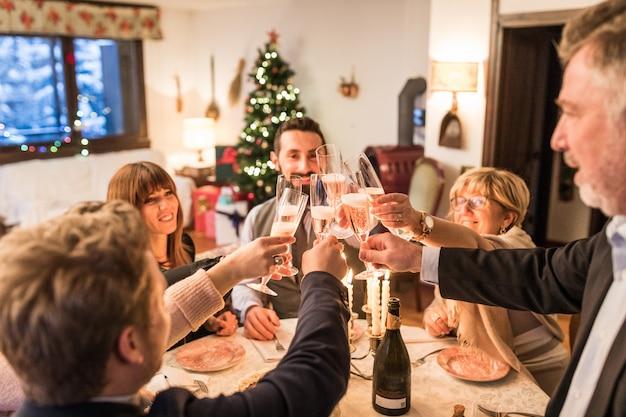 Familie, die weihnachten und neues jahr röstet und feiert