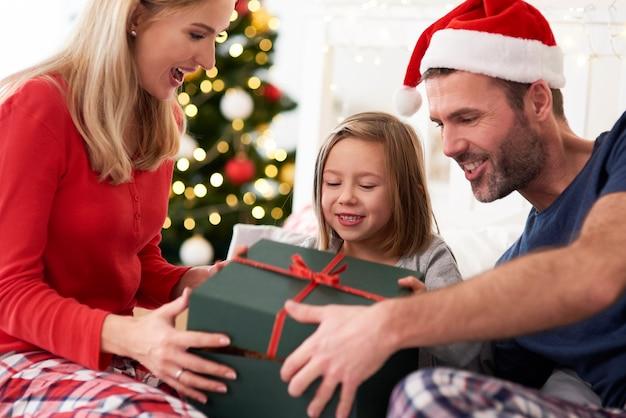 Familie, die weihnachten vom öffnen von geschenken im bett beginnt