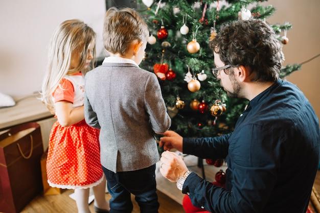 Familie, die weihnachtsbaum betrachtet