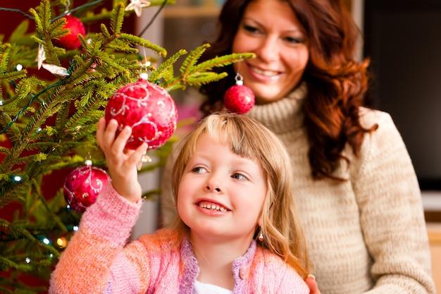 Familie, die weihnachtsbaum verziert