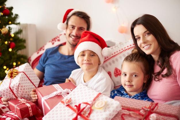 Familie, die weihnachtsmorgen im bett verbringt Kostenlose Fotos
