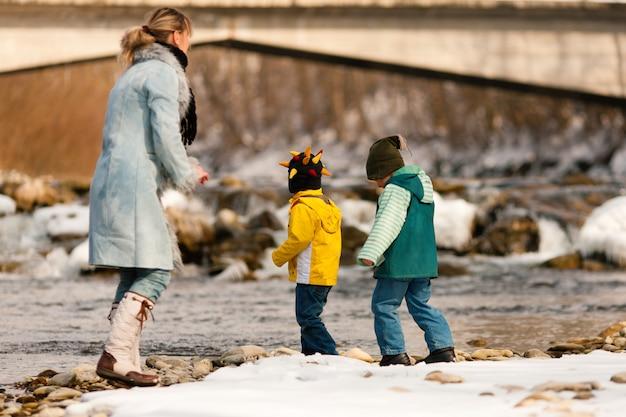 Familie, die winterweg am fluss hat