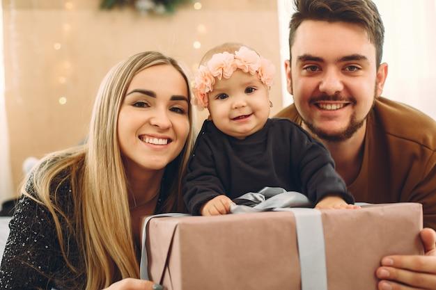 Familie, die zu hause auf einem bett mit geschenken sitzt