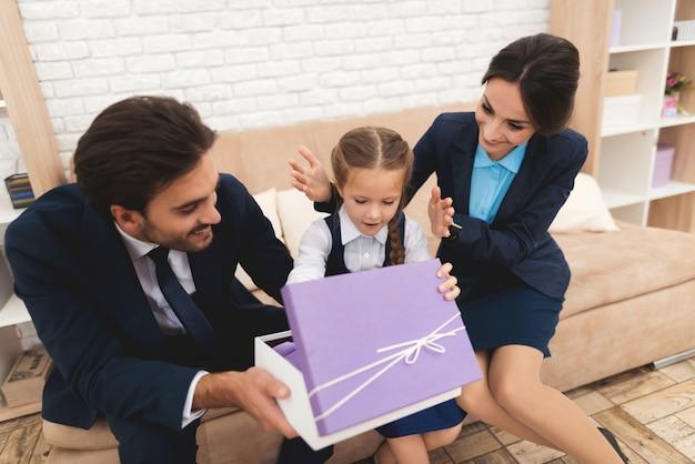 Familie, die zu hause der tochter auf sofa geschenkbox gibt