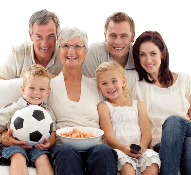 Familie, die zu hause ein fußballspiel aufpasst