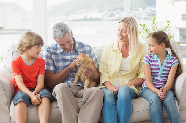 Familie, die zu hause mit katze auf sofa sitzt