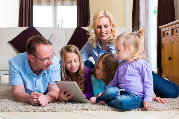 Familie, die zu hause mit tablet-computer spielt