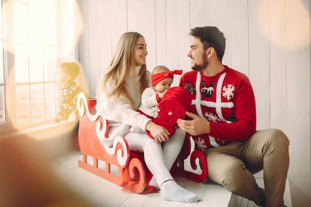Familie, die zu hause mit weihnachtsgeschenken sitzt