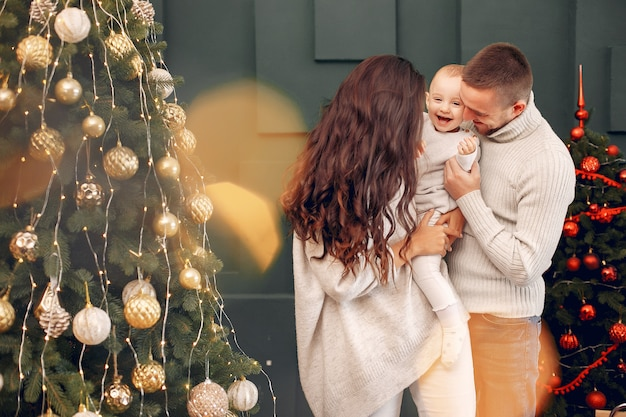 Familie, die zu hause nahe weihnachtsbaum sitzt