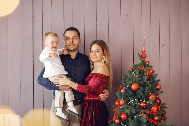 Familie, die zu hause nahe weihnachtsbaum steht