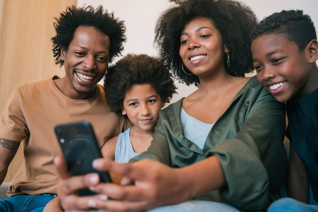 Familie, die zu hause selfie zusammen mit telefon nimmt.