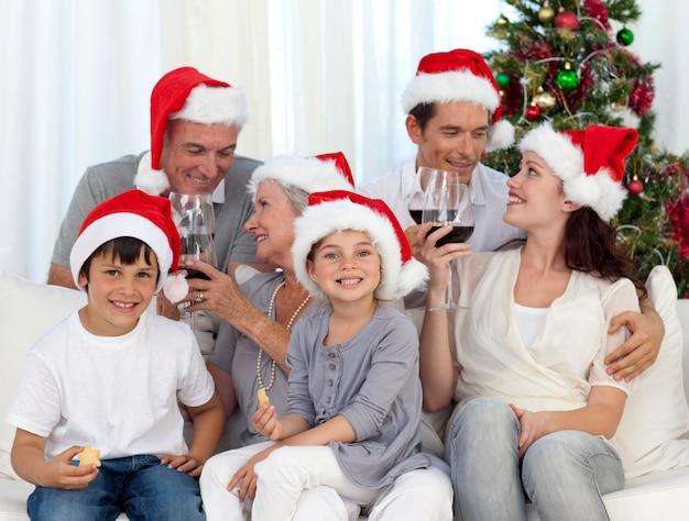 Familie, die zu hause weihnachten mit wein und bonbons feiert