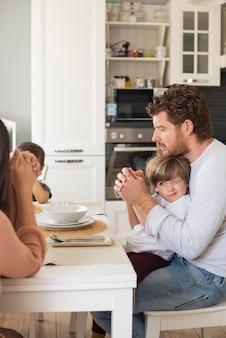 Familie, die zu hause zusammen ein gebet spricht