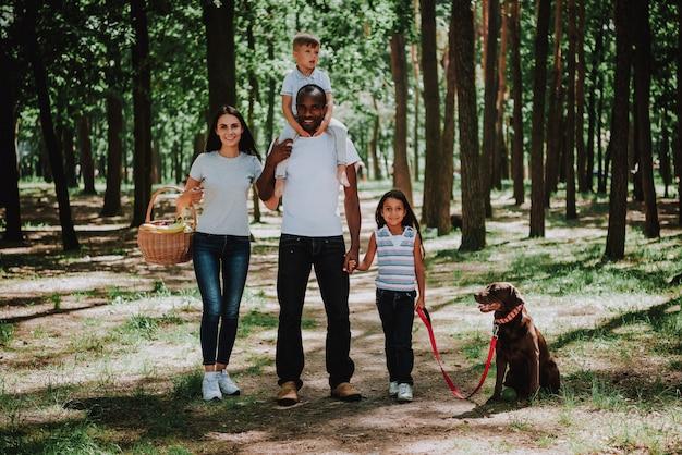 Familie, die zum picknick-sohn-reitvater-stutzen geht