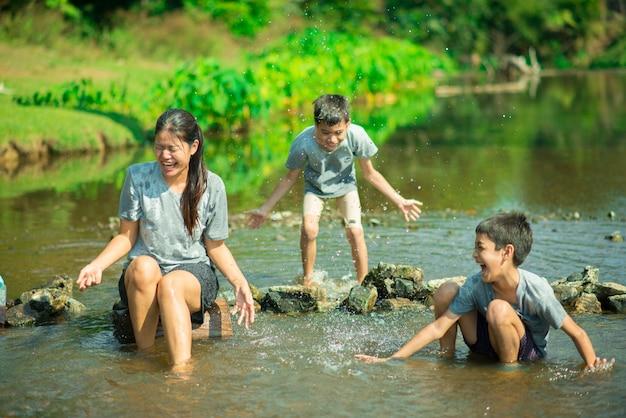 Familie, die zusammen am wasserfall im wald glücklich reist