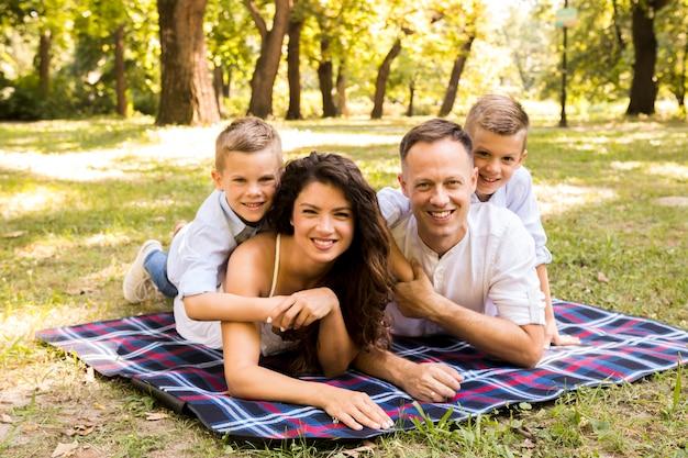 Familie, die zusammen auf picknickdecke aufwirft