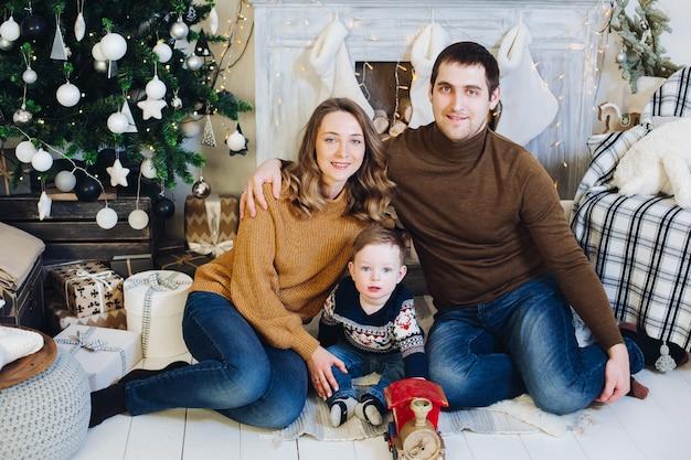 Familie, die zusammen auf sofa in verziertem weihnachtsbaum sitzt.