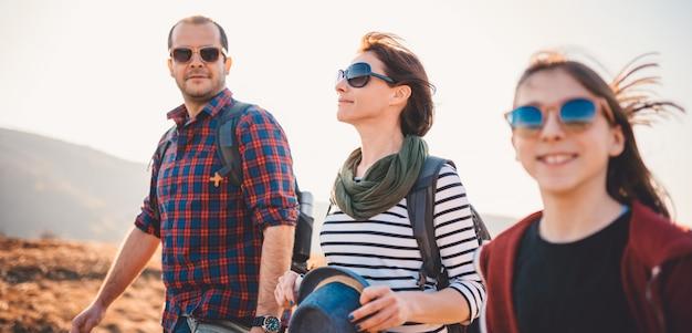 Familie, die zusammen beim wandern auf einem berg genießt