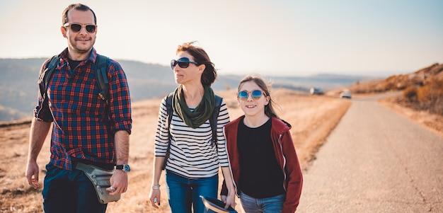 Familie, die zusammen durch die asphaltstraße an einem sonnigen tag wandert