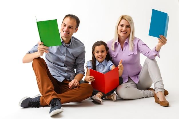 Familie, die zusammen ein buch liest, das zu hause auf dem boden liegt
