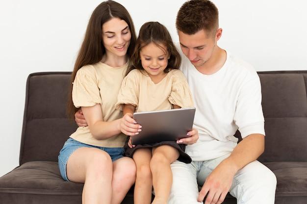 Familie, die zusammen ein tablett überprüft