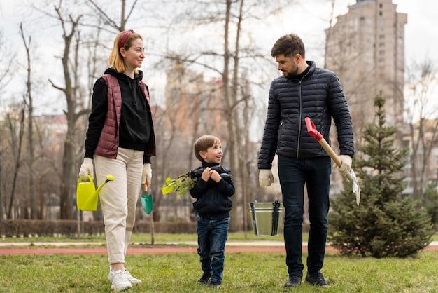 Familie, die zusammen einen baum pflanzen will