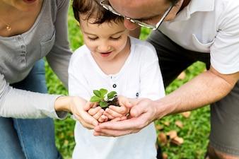 Familie, die zusammen einen Baum pflanzt