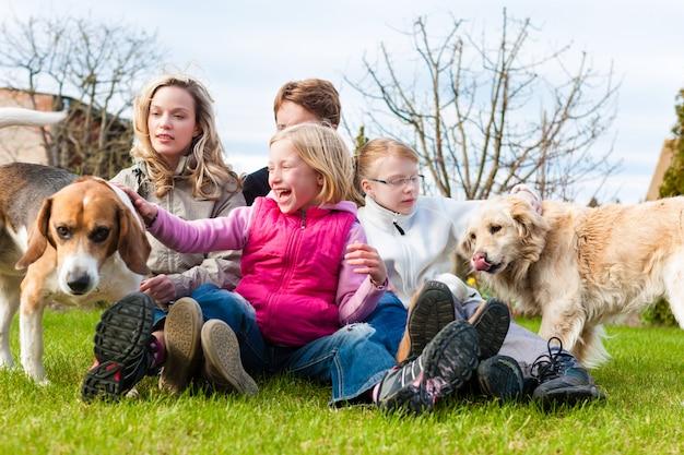 Familie, die zusammen mit hunden auf einer wiese sitzt
