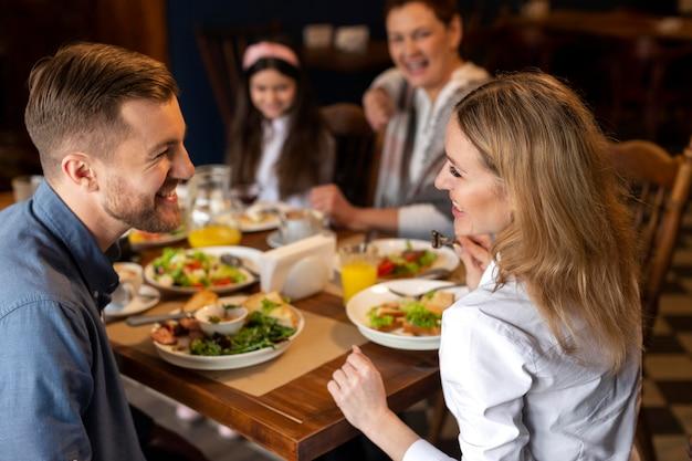 Familie, die zusammen mittleren schuss isst