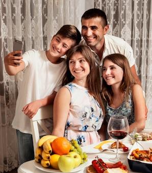 Familie, die zusammen selfie beim abendessen nimmt