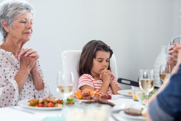 Familie, die zusammen vor mahlzeit betet