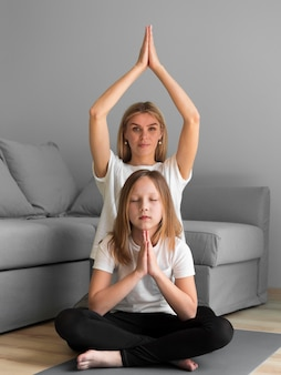 Familie, die zusammen yoga macht
