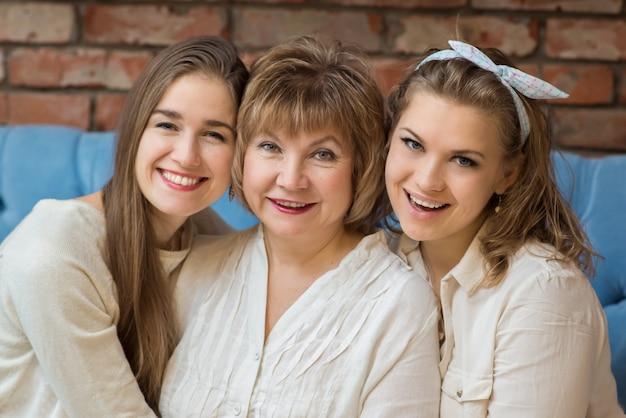 Familie: drei frauen, eine ältere mutter und erwachsene töchter sitzen lachend und umarmend auf der couch
