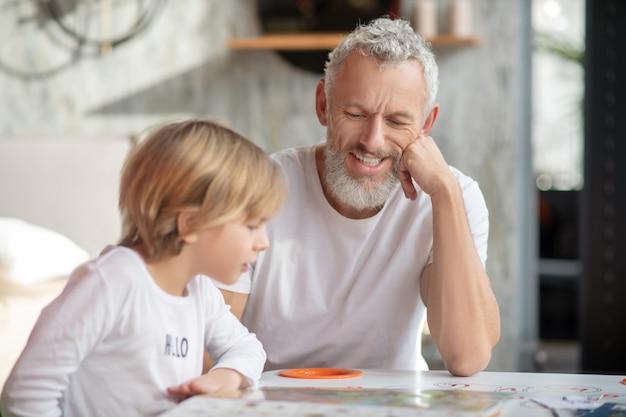 Familie. ein großvater unterstützt einen jungen, während er ein buch liest