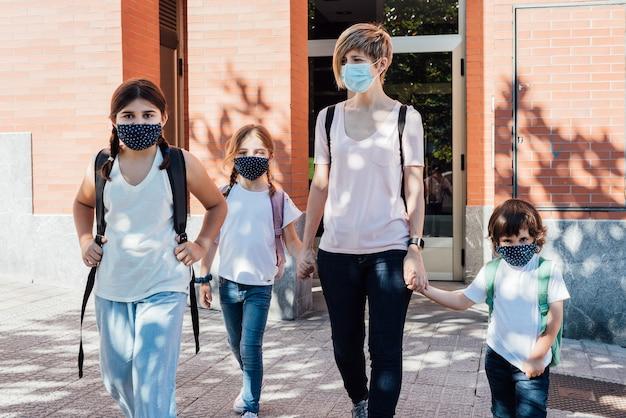 Familie einer mutter mit ihren drei kaukasischen kindern, die zu beginn des schuljahres wegen der covid19-coronavirus-pandemie das haus zur schule verlassen und masken tragen